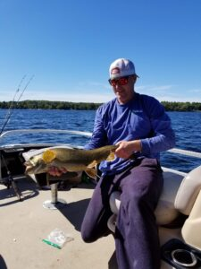 Maine fishing guide Charlie McGee struggling to hold a massive fish with his two hands.
